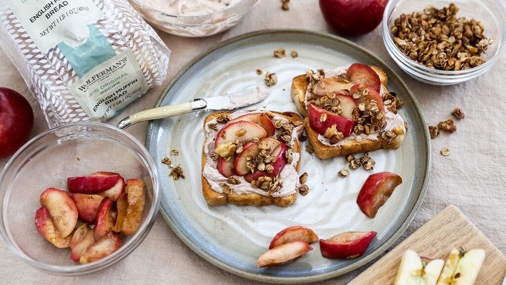 apple crisp image - apple crisp toast on a grey plate with ingredients surrounding it.